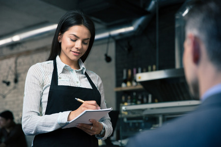 order in: Female waiter in apron writing order in restaurant Stock Photo