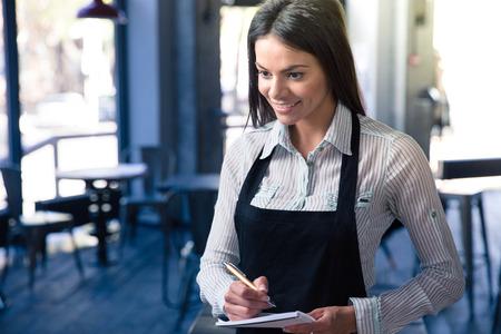 camarero: Una sonrisa hermosa camarero femenina en delantal con el bloc de notas y un bol�grafo en el caf�. Mirando a la c�mara