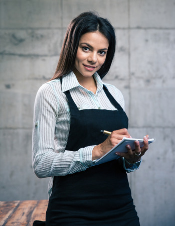 Happy beautiful female waiter in apron writing order. Looking at camera photo