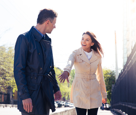 inviting: Happy young woman inviting man outdoors Stock Photo