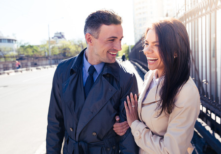 people laughing: Portrait of a young laughing couple walking outdoors