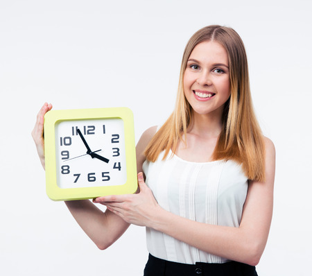 Smiling businesswoman holding big clock isolated on a gray background and looking at camera photo