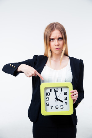 Angry businesswoman pointing finger on big clock over gray background and looking at camera photo