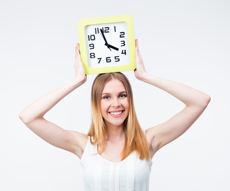 Happy woman holding big clock on head isolated on a gray background. Looking at camera photo
