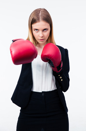 intimidating: Portrait of a businesswoman in boxing gloves over gray background. Hitting on camera