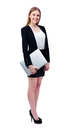 Full length portrait of a smiling businesswoman standing with laptop over white background and looking at camera photo
