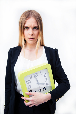 Serious businesswoman holding big clock over gray background and looking at camera photo