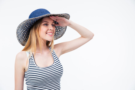 Happy cute woman in hat looking into distance over white background photo