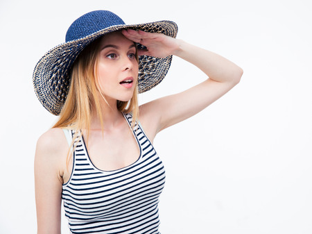 Young woman in hat looking into distance over white background photo