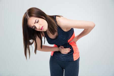 Fitness vrouw met pijn in de maag over grijze achtergrond