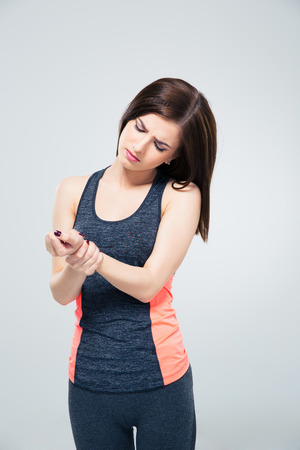 wrist pain: Fitness young woman with wrist pain over gray background