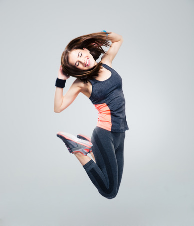 Glimlachende mooie sport vrouw springen over een grijze achtergrond