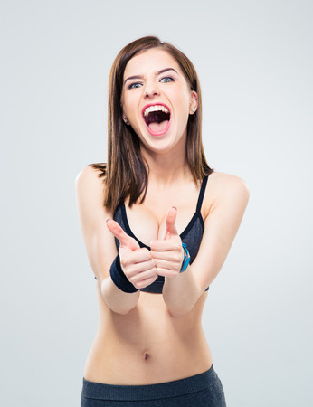 Crazy young woman showing thumbs up and screaming over gray background. Looking at camera