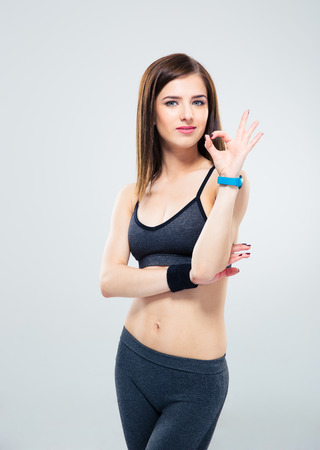 isolated sign: Happy cute sporty woman showing ok sign over gray background. Looking camera