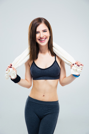 Smiling sporty woman with towel standing over gray background and looking at camera