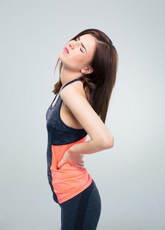 dolor de espalda: Fitness mujer que tiene dolor de espalda sobre fondo gris Foto de archivo