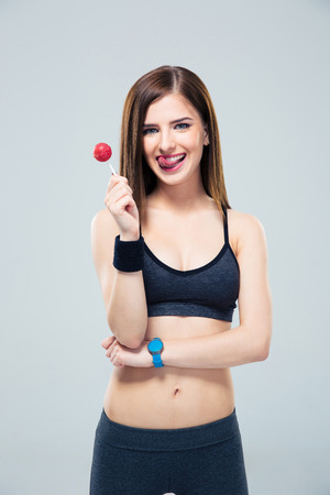 Pretty sporty woman holding lollipop and showing tonue over gray background. Looking at camera photo