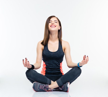 meditation isolated white: Happy fitness woman meditating isolated on a white background Stock Photo