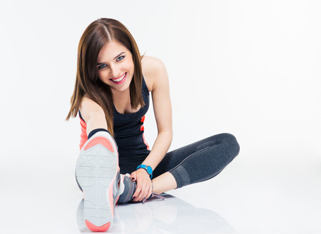 full: Happy fitness woman doing stretching exercises isolated on a white background. Looking at camera