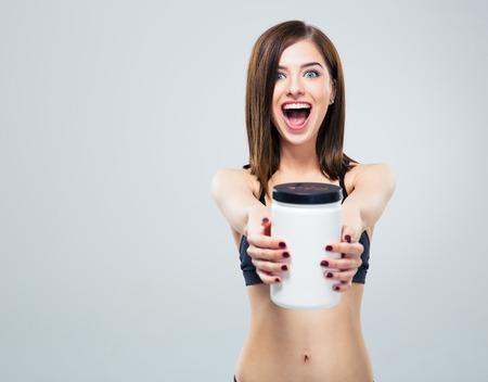 Vrolijk lachende sportieve vrouw met kruik eiwit over grijze achtergrond en kijken naar de camera Stockfoto - 41179278