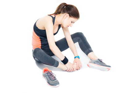 teen legs: Portrait of a sporty woman with pain on leg isolated on a white background Stock Photo