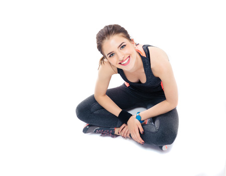 Smiling pretty woman sitting on the floor in sports wear. Isolated on a white background. Looking at camera photo