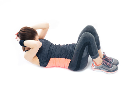 Sporty young woman doing abdominal exercises isolatedon a white background photo