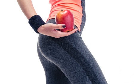 Closeup portrait of a woman`s body with apple isolated on a white background photo