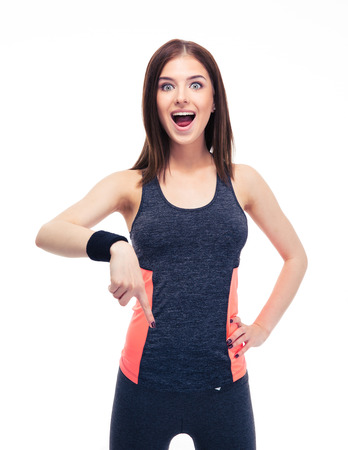 modern girls: Surprised fitness woman pointing finger down isolated on a white background. Looking at camera Stock Photo