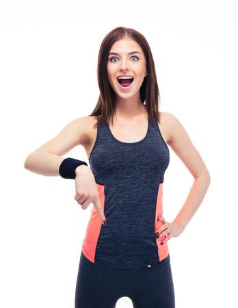 Verrast fitness vrouw wijzende vinger naar beneden geïsoleerd op een witte achtergrond. Kijkend naar de camera