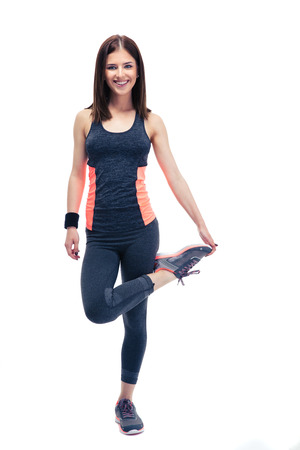 Full length portrait of a smiling sports woman stretching leg isolated on a white background. Looking at cameta photo