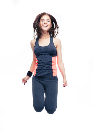 Smiling sports woman jumping isolated on a white background. Looking at camera