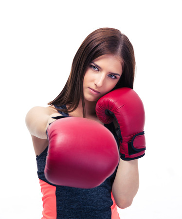 concetrated: Pretty woman punching in camera with boxing glove isolated on a white background. Looking at camera
