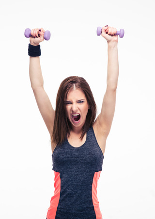 Screaming woman working out with dumbbells isolated on a white background. Looking at camera