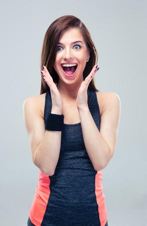 Surpris femme fitness heureux sur fond gris. Regardant la caméra
