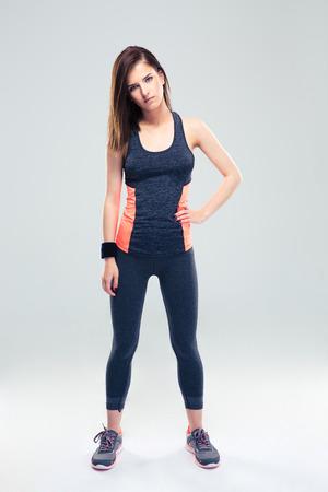 Pleine longueur portrait d'une belle femme de fitness debout sur fond gris et en regardant la caméra