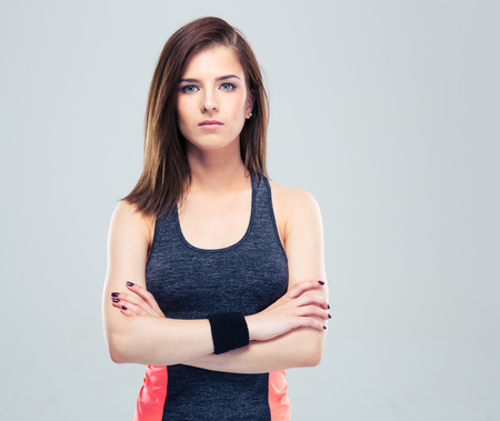 Cute young fitness woman in sports wear standing with arms folded on gray background and looking at camera