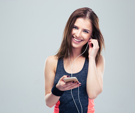 headphones: Happy sports woman with smartphone over gray background. Listening music in headphones