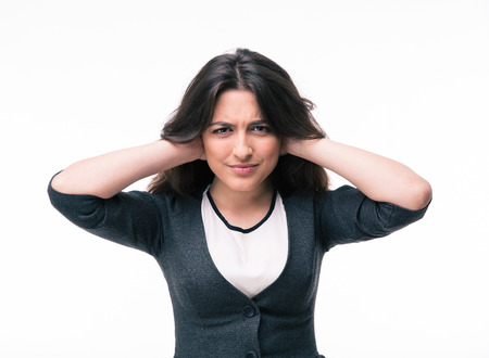 hands covering ears: Businesswoman covering her ears with hands isolated on a white background. Looking at camera Stock Photo