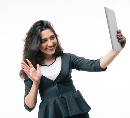 Happy businesswoman holding tablet computer and making greeting sign isolated on a white background photo