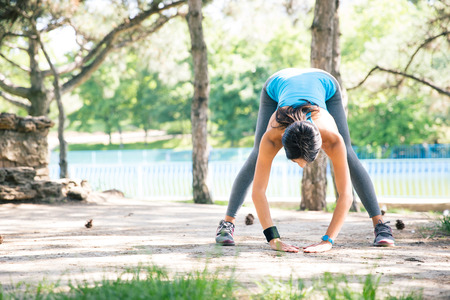 concetrated: Sporty woman doing stretching exercise outdoors in park Stock Photo