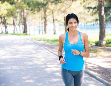 Lachende sportieve vrouw lopen buiten in park