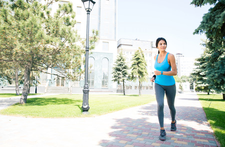 backgruond: Full length portrait of a happy sports woman running outdoors with building on backgruond