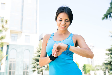 looking at watch: Happy sporty woman using smart watch outdoors