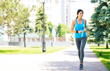 running pants: Full length portrait of a young sports woman running outdoors with building on backgruond Stock Photo