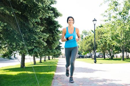 mujer alegre: Retrato de cuerpo entero de una mujer deportiva feliz corriendo al aire libre Foto de archivo