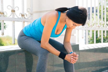 mujer descansando: Joven deportiva en reposo despu�s de correr al aire libre
