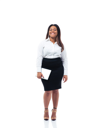 Full length portrait of a smiling afro american businesswoman holding tablet computer over whiet background. Looking at camera Stok Fotoğraf