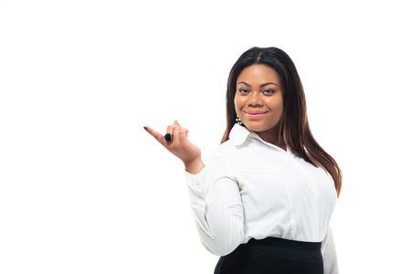 Gelukkig Afro-Amerikaanse zakenvrouw wijzende vinger weg die op een witte achtergrond. Kijken naar de camera