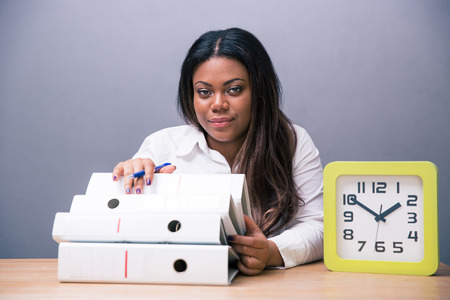 African businesswoman sitting at the table with pen and folders over gray background. Looking at camera photo